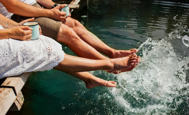 Homem e mulher brincando na água com os pés
