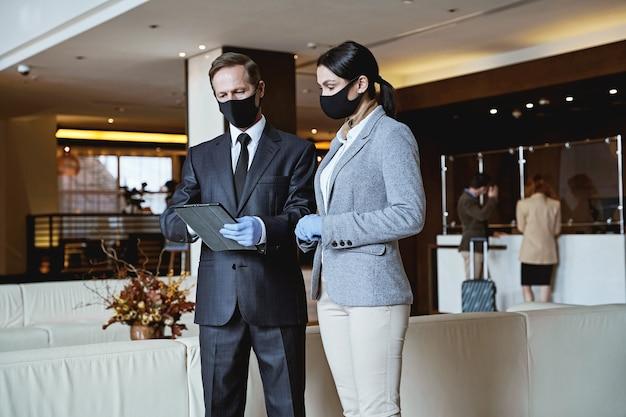 Homem e mulher calmos com máscaras de tecido e luvas de borracha olhando para a tela do tablet no saguão de um hotel