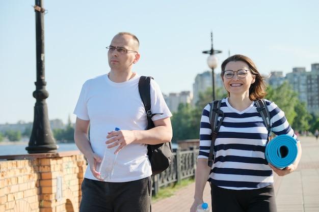 Homem e mulher caminhando ao ar livre em roupas esportivas com mochilas