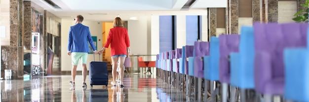 Homem e mulher caminhando com uma mala pelo hotel