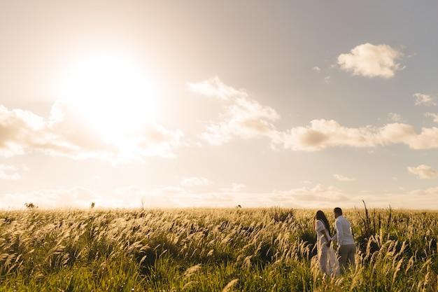 Homem e mulher caminhando em um prado verde em um dia ensolarado