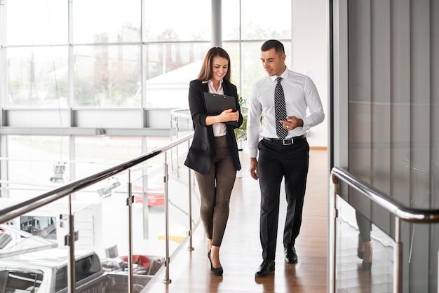Homem e mulher caminhando juntos na concessionária