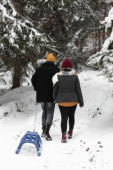 Homem e mulher caminhando na floresta com trenó por trás do tiro