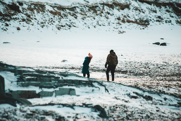 Homem e mulher caminhando no chão coberto de neve durante o dia