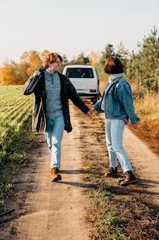 Homem e mulher caminhando perto de sua van