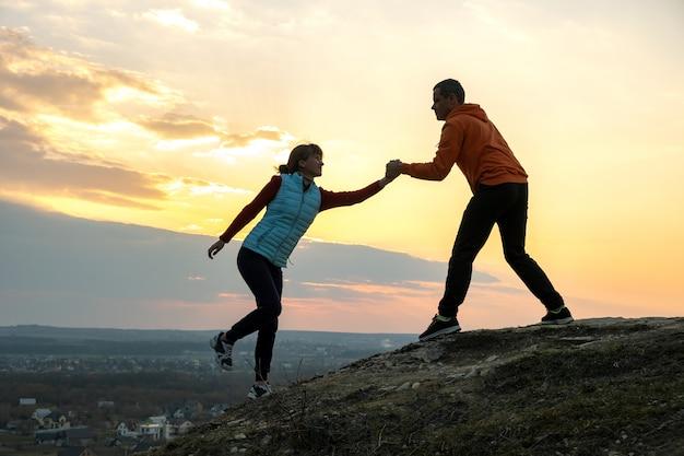 Homem e mulher caminhantes ajudando uns aos outros para escalar pedra ao pôr do sol nas montanhas