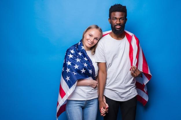 Homem e mulher cobertos com a bandeira americana isolada na parede azul. unidade do povo americano.