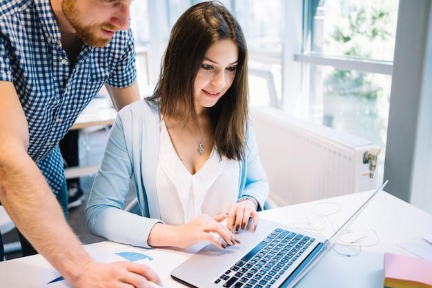 Homem e mulher colaborando no laptop