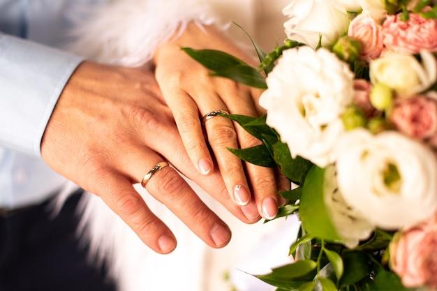Homem e mulher com aliança de casamento de mãos dadas