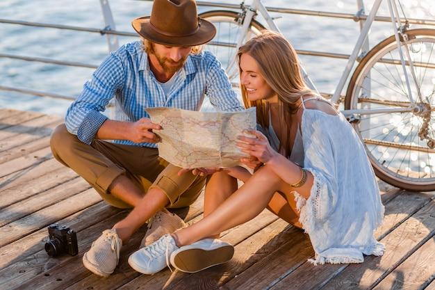 Homem e mulher com cabelo loiro boho hipster estilo moda se divertindo juntos, olhando no mapa