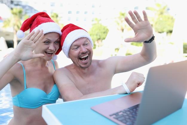 Homem e mulher com chapéu de papai noel acenando com a mão para a tela do laptop na piscina