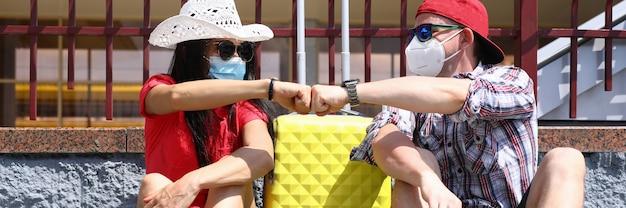 Homem e mulher com chapéu sentados na calçada da plataforma da estação de trem com a mala amarela na máscara protetora punho com punho