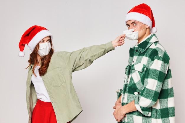 Homem e mulher com chapéus de ano novo, máscaras médicas, quarentena, feriado, ano novo
