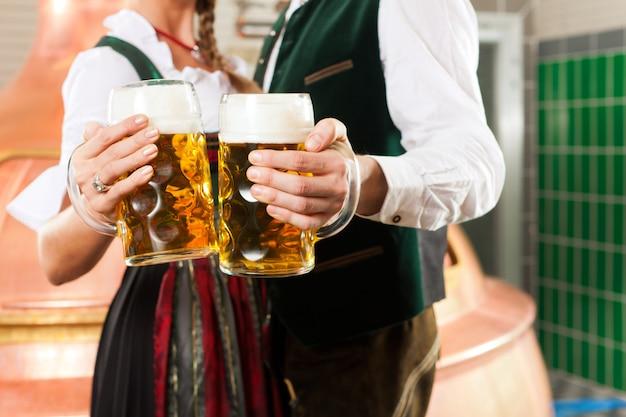 Homem e mulher com copo de cerveja na cervejaria