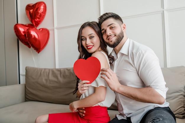 Homem e mulher com coração em forma de cartão de dia dos namorados e balões vermelhos, sentado no sofá em casa