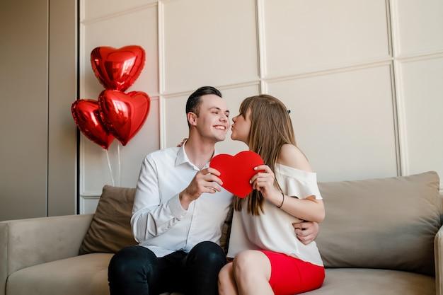 Homem e mulher com coração vermelho em forma de cartão de dia dos namorados e balões em casa no sofá