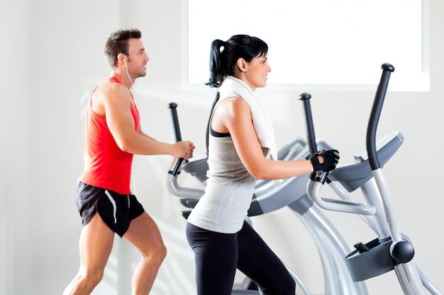 Homem e mulher com elíptica cross trainer no ginásio