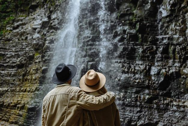 Homem e mulher com jaqueta marrom olhando para a cachoeira