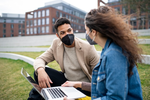 Homem e mulher com laptop trabalhando e conversando ao ar livre no parque da cidade, o conceito de coronavírus.