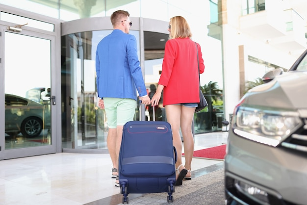 Homem e mulher com mala saem do táxi para o prédio do aeroporto