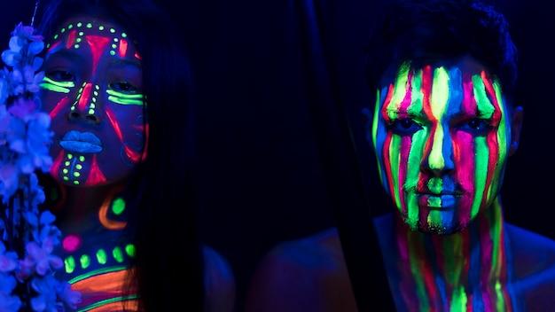 Homem e mulher com maquiagem fluorescente