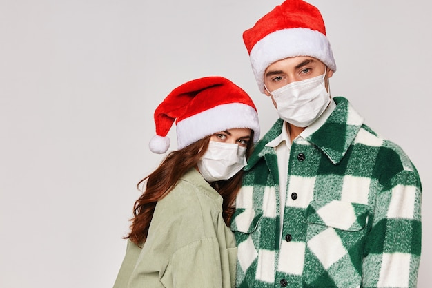 Homem e mulher com máscaras médicas, chapéus de natal, abraços