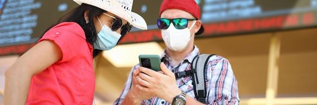 Homem e mulher com máscaras protetoras médicas na estação de trem ao lado do quadro de informações.