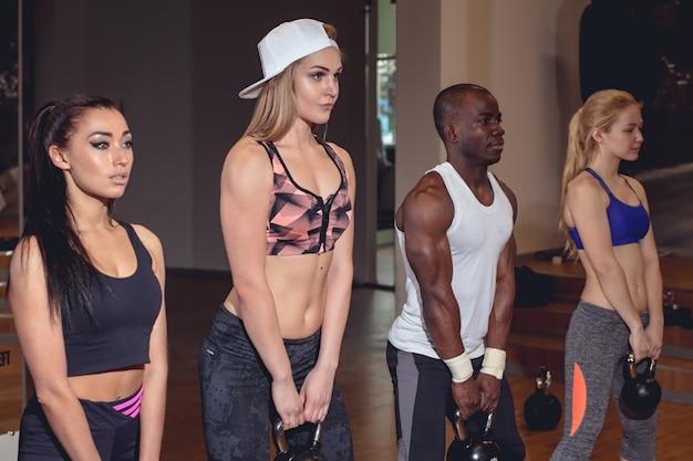 Homem e mulher com o treinador no treinamento funcional kettlebell no centro de fitness
