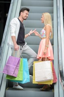 Homem e mulher com pacotes sobem a escada rolante.