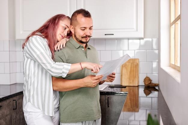 Homem e mulher com papéis na cozinha, jovem casal caucasiano verificando as contas