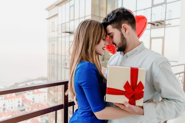 Homem e mulher com presente e coração vermelho em forma de balões na varanda em casa