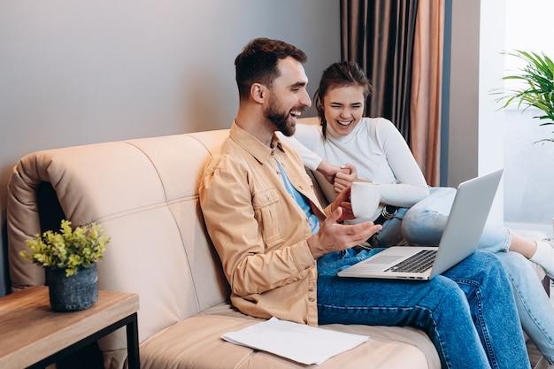 Homem e mulher com roupas casuais sentam-se no sofá de couro na moderna sala de estar e riem de algo no laptop masculino