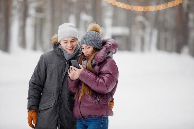 Homem e mulher com roupas de inverno olhando para o smartphone em um parque nevado