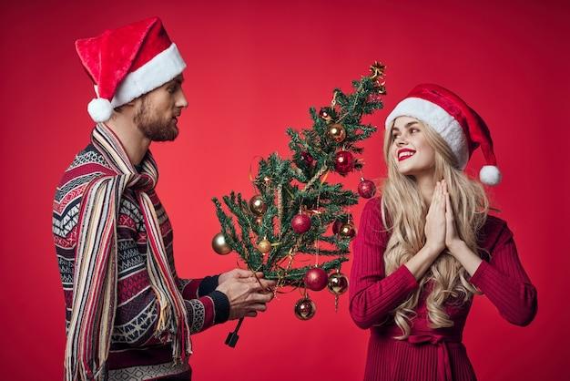 Homem e mulher com roupas de natal, presente de feriado, fundo vermelho