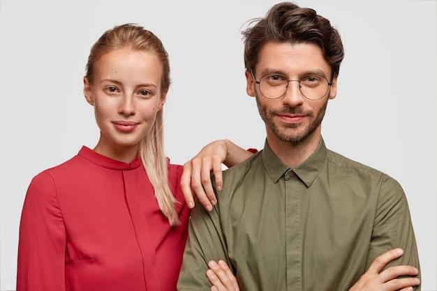 Homem e mulher com roupas formais posando Foto gratuita