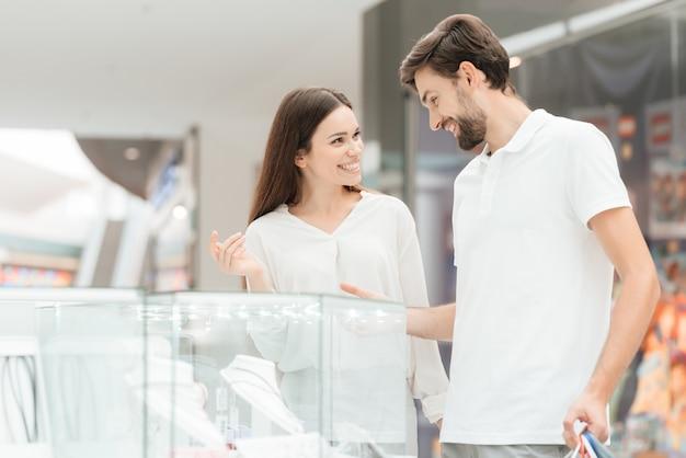 Homem e mulher com sacos de compras em shopping center.