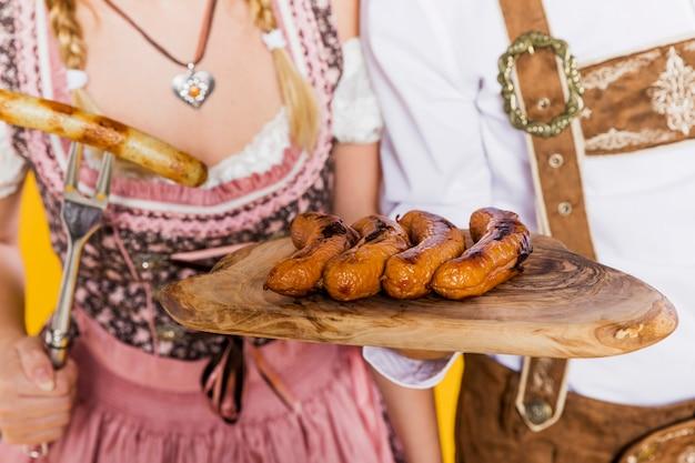 Homem e mulher com salsichas da baviera tradicionais