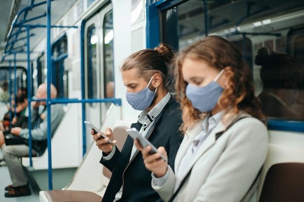 Homem e mulher com smartphones sentados em um vagão do metrô