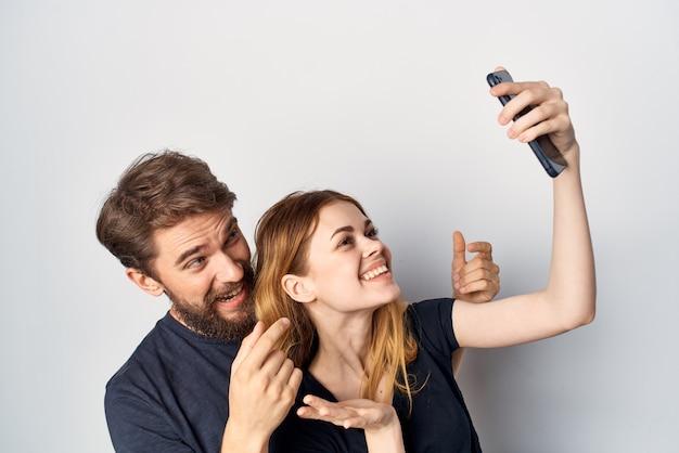 Homem e mulher com um telefone na mão fundo isolado emoções
