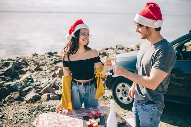Homem e mulher comemorando o natal enquanto bebem champanhe perto da água