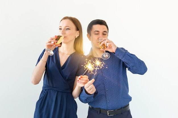 Homem e mulher comemorando o natal ou a festa de véspera de ano novo com luzes de bengala e taças de champanhe no fundo branco.