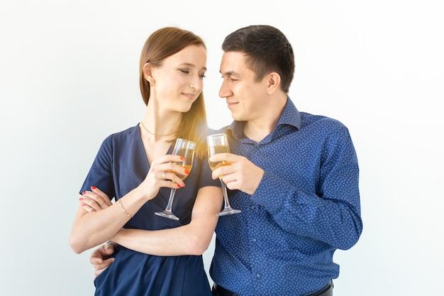 Homem e mulher comemorando o natal ou a festa de véspera de ano novo com taças de champanhe no fundo branco.
