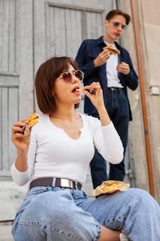 Homem e mulher comendo hambúrgueres ao ar livre