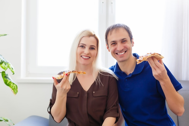 Homem e mulher comendo pizza e curtindo a noite