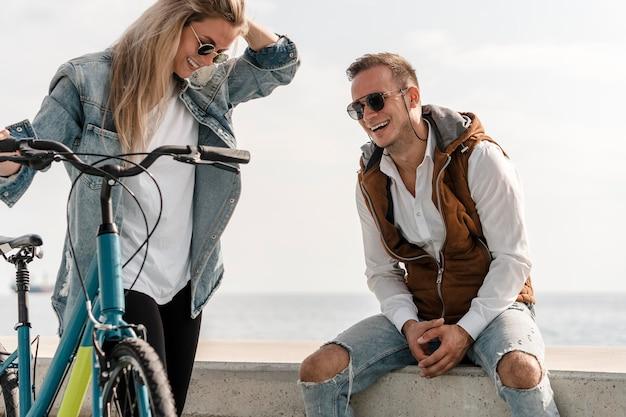 Homem e mulher conversando ao lado de uma bicicleta