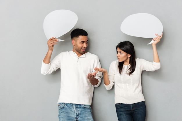 Homem e mulher conversando e segurando bolhas em branco