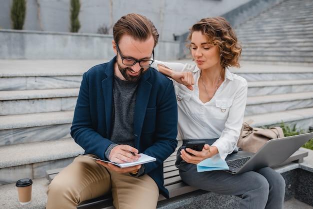 Homem e mulher conversando sentados na escada no centro urbano da cidade