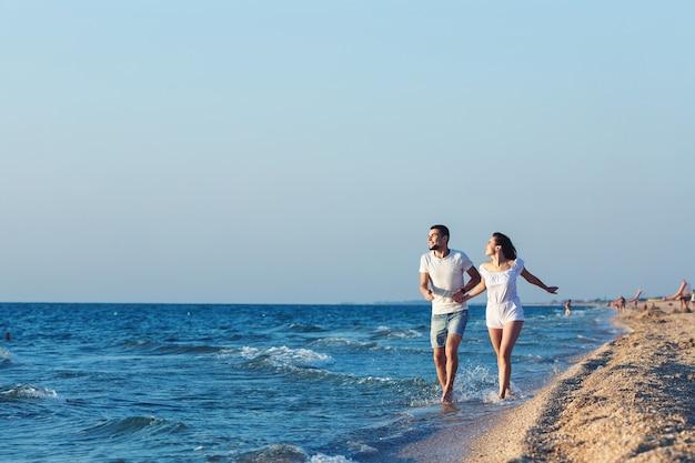 Homem e mulher correm alegremente ao longo da costa do mar.