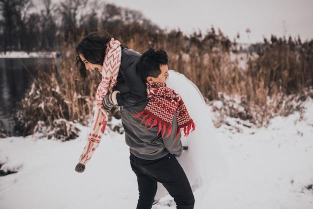 Homem e mulher correndo, deitado na neve, rindo, brincando e se divertindo jogando bolas de neve