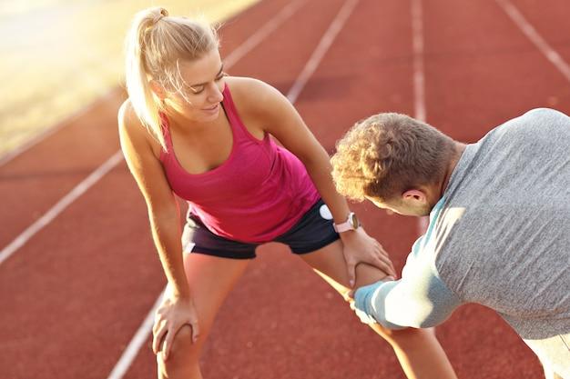 Homem e mulher correndo em pista ao ar livre